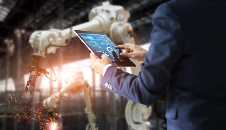 Ein Mann im Anzug steuert einen Roboterarm in einer Fabrik über ein Tablet