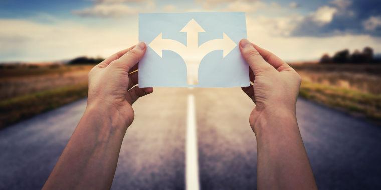 Zwei Hände halten eine Karte in der Hand, worauf drei Pfeile abgebildet sind. Ein Pfeil zeigt geradeaus, einer nach links und einer nach rechts. Im Hintergrund befindet sich eine Straße und ein sonniger Himmel
