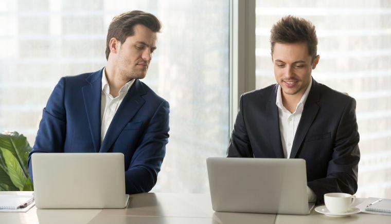 Zwei Geschäftsleute sitzen vor ihrem Laptop; einer schaut dem anderen über die Schulter, um Hilfe zu bekommen